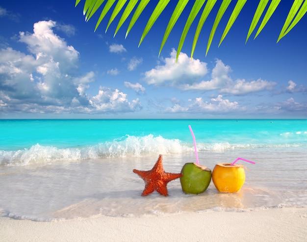 Coquetéis de coco suco e estrela do mar na praia tropical