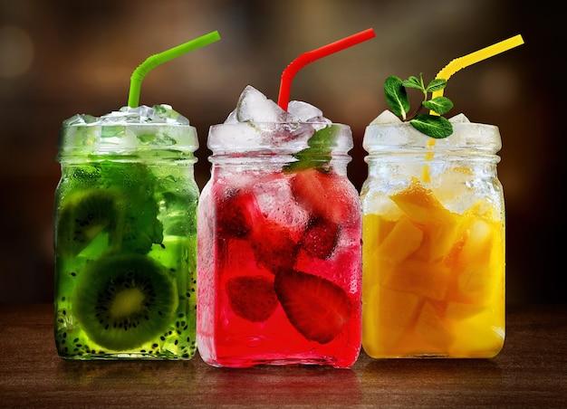 Coquetéis de frutas refrescantes em potes de vidro na mesa de madeira