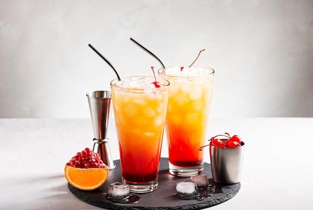 Coquetéis de gelo tequila ao nascer do sol em uma mesa de concreto cinza ao lado de uma jigger e uma cereja