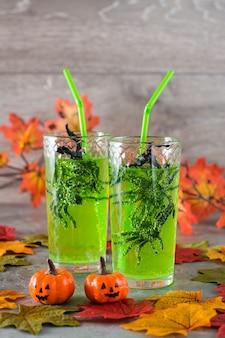Coquetéis de halloween. aranhas negras em copos com limonada verde, abóboras e folhas de outono