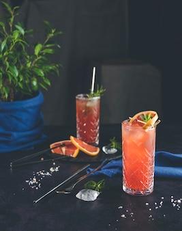 Coquetéis de mezcal paloma de toranja rosa em copos altos em fundo escuro elegante