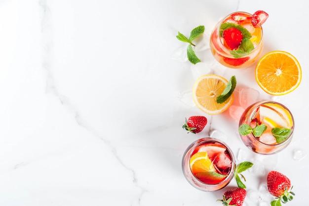 Coquetéis de sangria frios brancos, rosa e vermelhos com frutas frescas, frutas e min