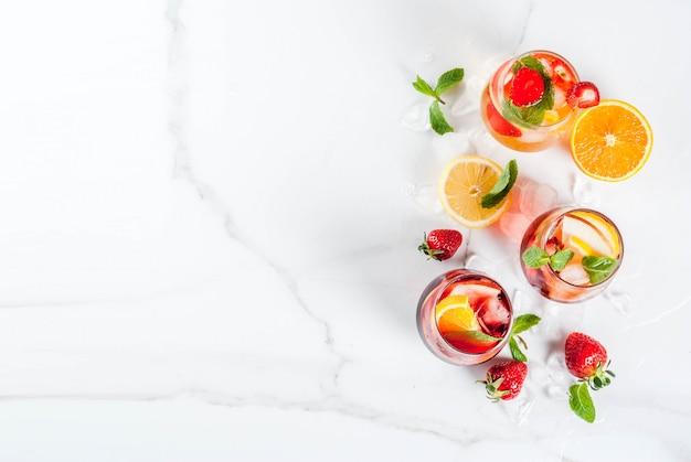 Coquetéis de sangria rosa e vermelho brancos frios com frutas frescas e hortelã.