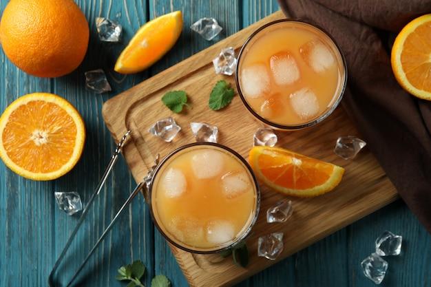 Coquetéis de tequila ao nascer do sol e ingredientes na mesa de madeira