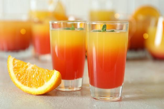 Coquetéis de tequila ao nascer do sol na mesa texturizada branca, close-up