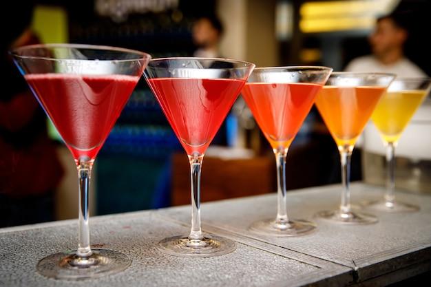 Coquetéis diferentes em copos triangulares no bar.