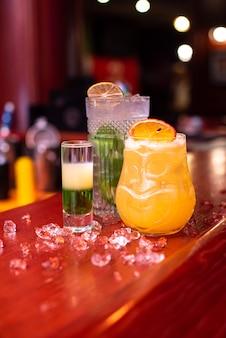 Coquetéis gelados com hortelã-limão e gelo em um copo com gotas de bebida alcoólica no bar