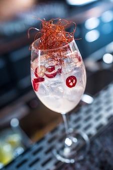 Coquetéis gin tônicos em taça de vinho com chili no balcão do bar do filhote de cachorro ou restaurante.