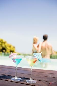Coquetéis na beira da piscina e casal na piscina