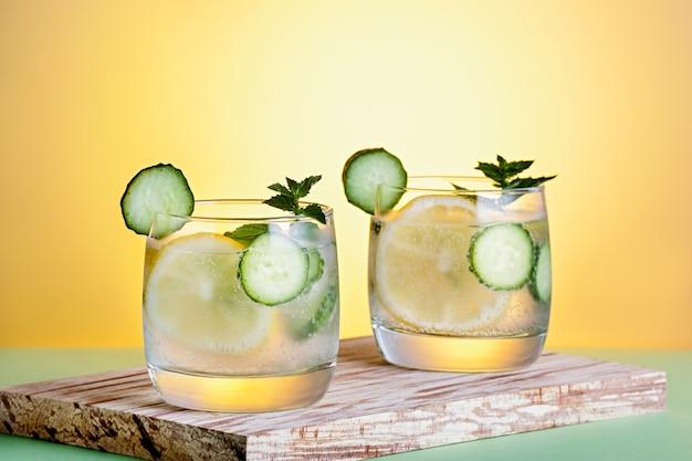 Coquetéis não alcoólicos refrescantes de verão com limão, pepino e hortelã, close-up em fundo amarelo