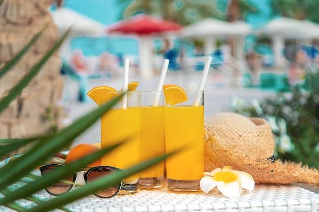 Coquetéis, óculos escuros, chapéu de palha e frutas frescas em uma tigela branca à beira da piscina
