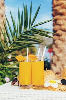 Coquetéis, óculos escuros e frutas frescas em uma tigela branca à beira da piscina