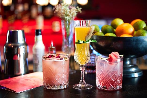 Coquetéis rosa e amarelos modernos no bar.