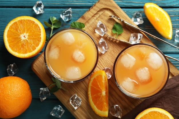 Coquetéis tequila sunrise e ingredientes na mesa de madeira