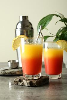 Coquetéis tequila sunrise em mesa texturizada cinza
