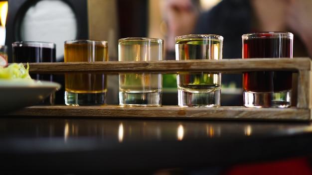 Coquetéis transparentes multicoloridos, um conjunto de doses em uma fileira, seis porções em um suporte de madeira, substrato. bebida para o menu do restaurante, bar, café