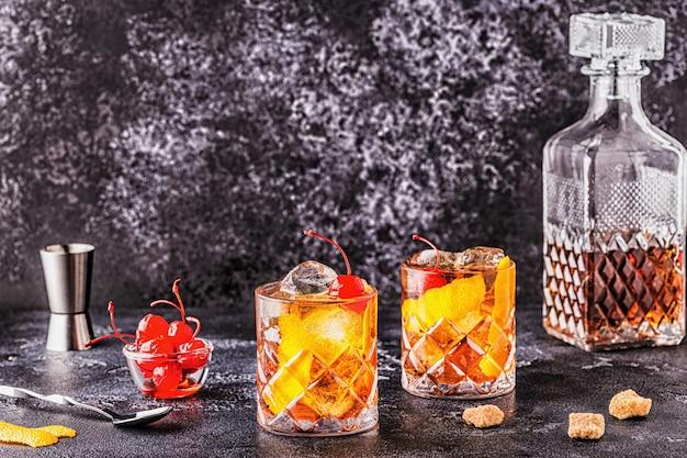 Coquetel à moda antiga com cerejas e torção de laranja, foco seletivo.