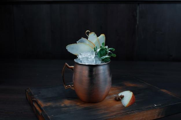 Coquetel alcoólico com rum branco com pedaços de gelo com fatias de pêra doce fresca e canela em uma caneca vintage de metal em uma mesa vintage marrom em um restaurante. bebida gourmet.