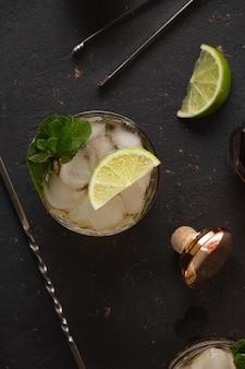 Coquetel alcoólico com rum e gelo e hortelã no escuro
