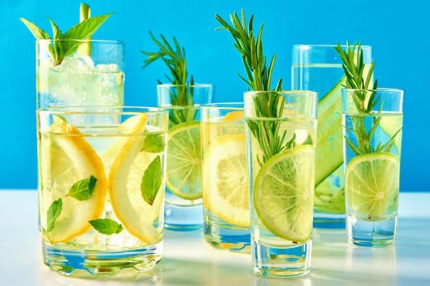 Coquetel alcoólico de verão gin tônica com limão e alecrim sobre fundo azul