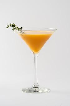 Coquetel alcoólico decorado com tomilho em taça de vidro
