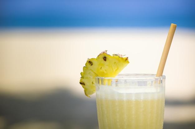 Coquetel alcoólico em vidro com fatia de abacaxi na praia.