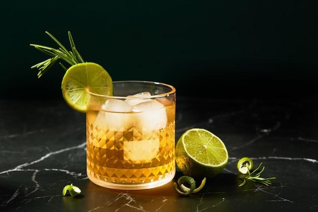 Coquetel alcoólico ou não alcoólico com limão e alecrim em mesa de mármore escuro