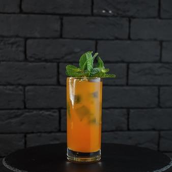 Coquetel alcoólico tropical de laranja com pedaços de gelo com suco de grapefruit com tônica com gin com vodka decorado com folhas de menta na mesa do bar. mistura incomum de ingredientes