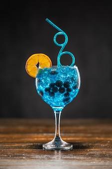 Coquetel azul com mirtilo, fatia de laranja e gelo em um copo na mesa de madeira
