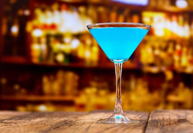 Coquetel azul na mesa de madeira de um bar