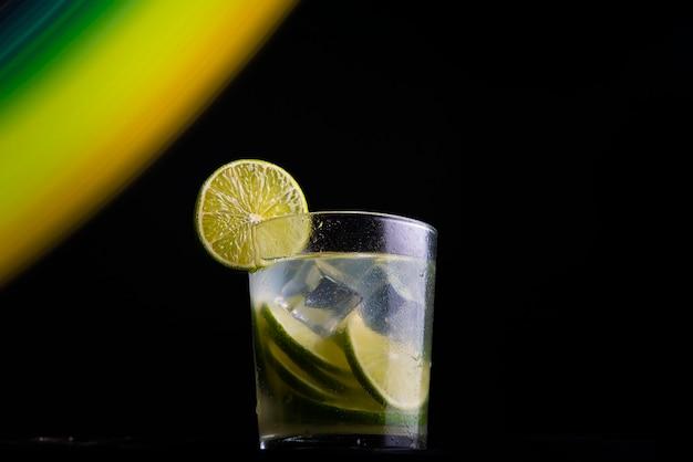 Coquetel brasileiro chamado caipirinha. com limão, gelo e cachaça em fundo escuro com luzes coloridas. copie o espaço