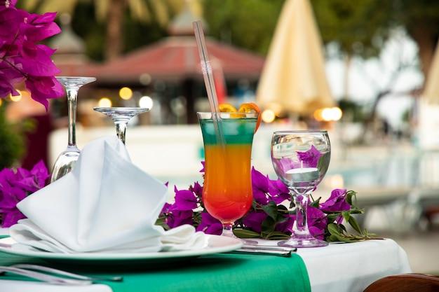 Coquetel brilhante em várias camadas com um canudo em uma mesa servida para um coquetel