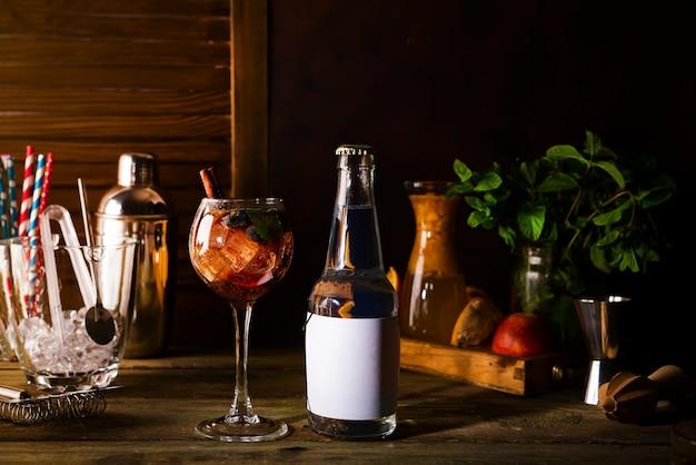 Coquetel com chá gelado e gelo em um copo com uma garrafa de tônica no fundo escuro de madeira