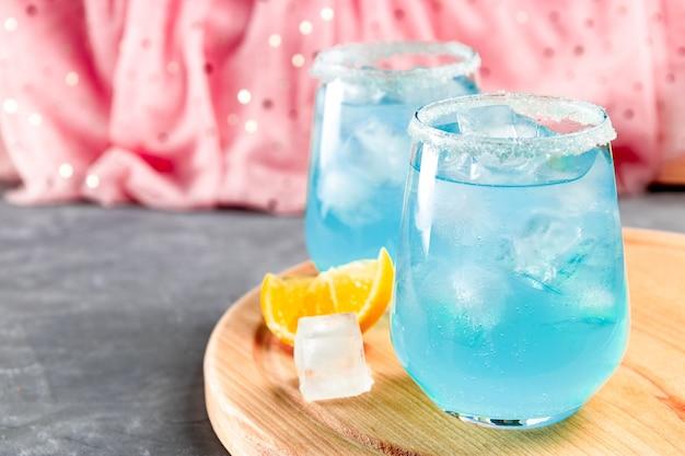 Coquetel com gelo e curaçao azul em um rosa delicado