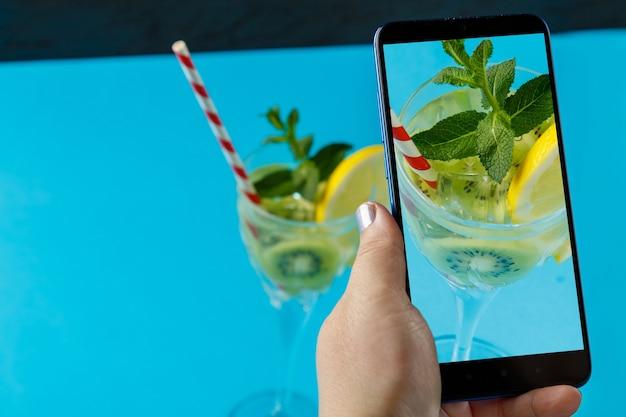 Coquetel com hortelã, pepino e limão em um copo em uma superfície azul, uma mão feminina tira fotos