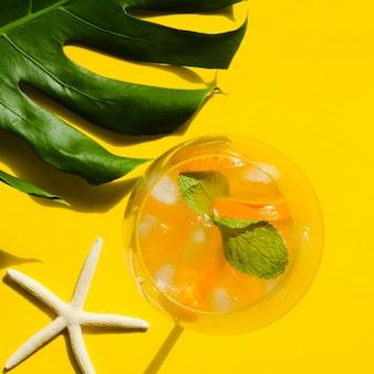 Coquetel com laranja, hortelã e gelo perto da estrela do mar