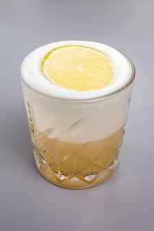 Coquetel com lima e espuma branca em um copo de vidro.