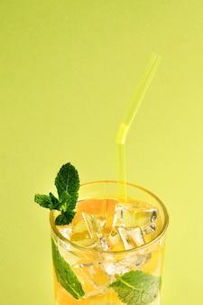 Coquetel com limão e hortelã sobre um fundo verde. copie o espaço.