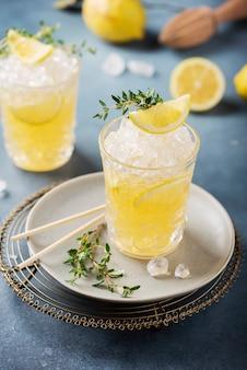 Coquetel com limão, timo e gelo picado no fundo escuro, conceito de bar e imagem de foco seletivo