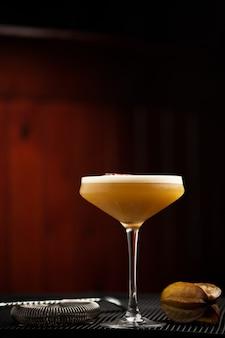 Coquetel com maracujá em copo alto na barra de fundo marrom close up