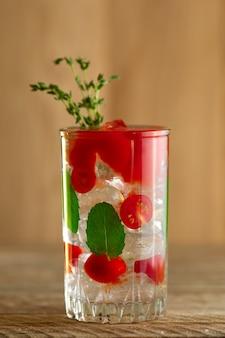 Coquetel com vodka, tomate, hortelã e cubos de gelo na mesa de madeira
