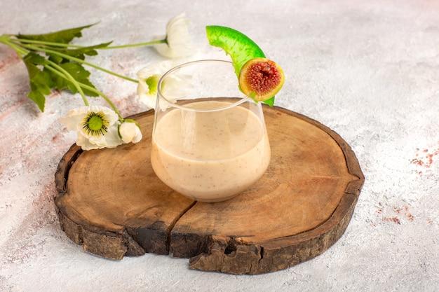 Coquetel cremoso de visão frontal de perto dentro de um pequeno copo com flores na superfície branca