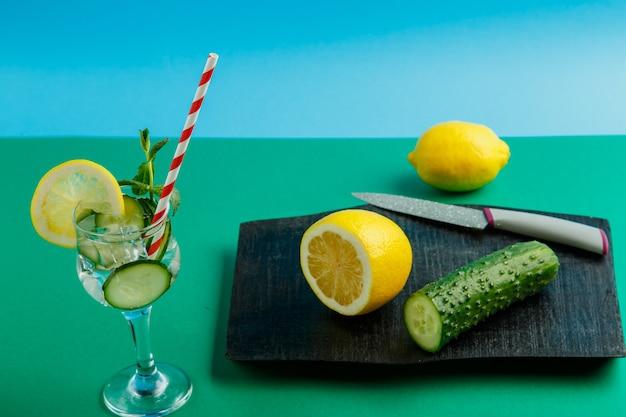 Coquetel de água de pepino com limão e hortelã em um copo em um guardanapo em uma superfície verde ao lado de um limão e pepinos em um guardanapo e uma faca