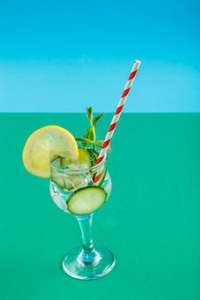 Coquetel de água de pepino com limão e hortelã em um copo em um guardanapo sobre uma superfície verde