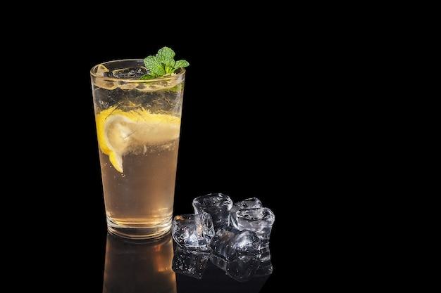 Coquetel de álcool com limão e hortelã em um fundo preto