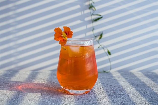 Coquetel de álcool italiano aperol spritz com cubos de gelo e flores