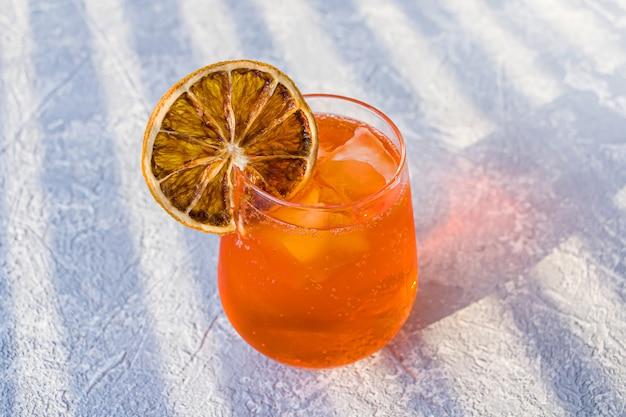 Coquetel de álcool italiano aperol spritz com cubos de gelo e uma fatia de laranja seca