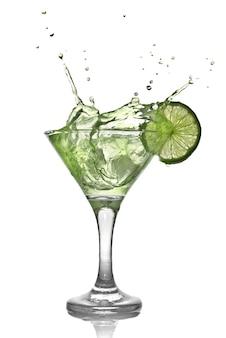 Coquetel de álcool verde com splash e limão verde isolado no branco
