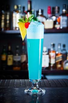 Coquetel de bebida azul com espuma decorada de abacaxi e cereja em copo grande, fechar no balcão do bar.