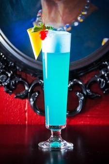 Coquetel de bebida azul com espuma decorada de abacaxi e cereja em copo grande na imagem da moldura.